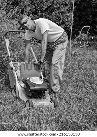 Man mowing overgrown lawn in his yard.