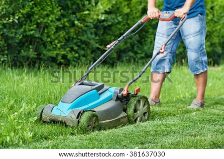 Man mowing the lawn with blue lawnmower in summertime - closeup - stock photo