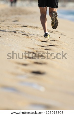 Man muscled legs running on the sand of a beach