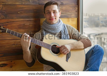 man musician with guitar, sitting on the window, a wooden background, music, looks into the frame interior of the house,very soft focus