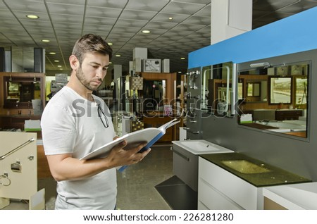 Man observes catalog in indoor wc and plumbing store - stock photo