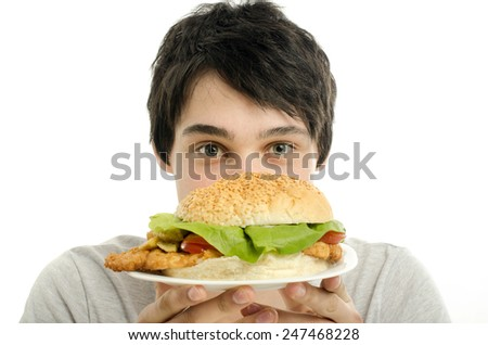Man offering a big hamburger, fast food, take out for you - stock photo