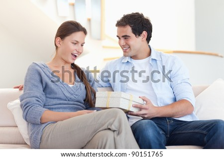 Man offering a gift to his fiance in their living room