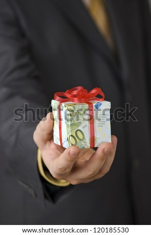 Man offering an expensive gift box wrapped in euro banknotes - stock photo