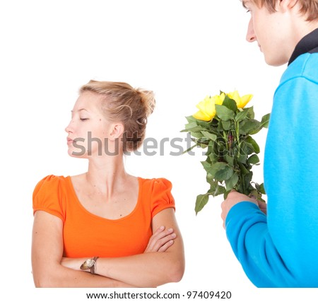 man offering flowers to his girlfriend who is very upset after argument - stock photo
