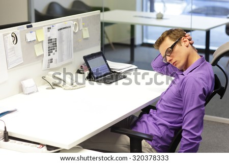 man office worker relaxing neck during work with tablet in his office