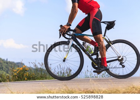 Man on a bicycle on a road between the beautiful mountains