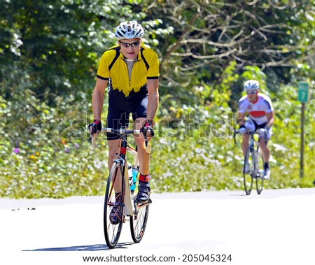 Man on a bicycle standing to climb a mountain during a cycling event. - stock photo