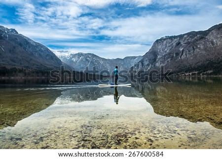 man on a canoe on a mountain lake - stock photo