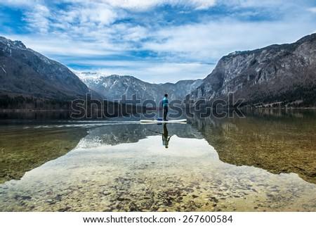 man on a canoe on a mountain lake - stock photo