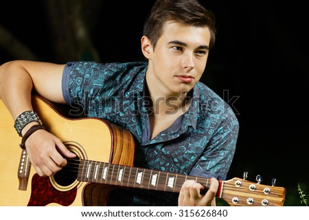 Man on a grass with a guitar - stock photo