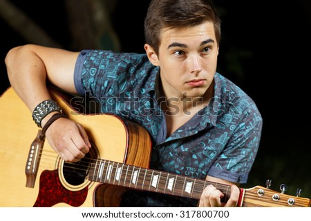 Man on a grass with a guitar
