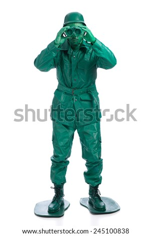Man on a green toy soldier costume standing with binocolous isolated on white background. - stock photo