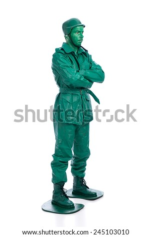 Man on a green toy soldier costume with arms crossed isolated on white background. - stock photo