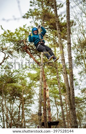 Man on a high wire crossing in an adventure park - stock photo