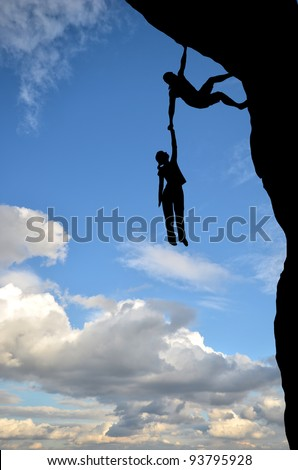 man on a rock holding the hand of a woman dangling over the precipice in the sky - stock photo