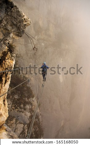 man on a suspension path in via-ferrata activity - stock photo