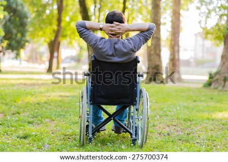 Man on a wheelchair relaxing in a park - stock photo