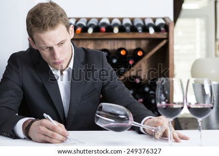 man on a wine tasting session on the visual phase is writing down in a wine tasting sheet at a restaurant - focus on the man face