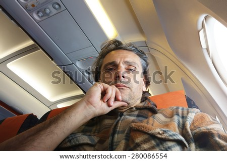 Man on airplane looking at camera