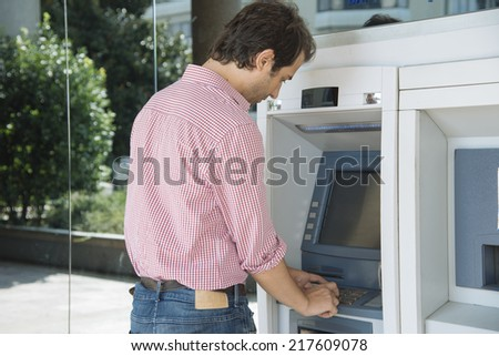 man on atm getting cash - stock photo