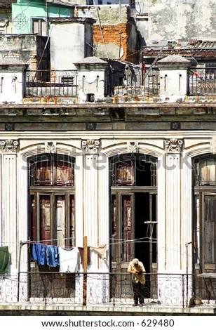Man on balcony of old crumbling building. Habana, Cuba - stock photo
