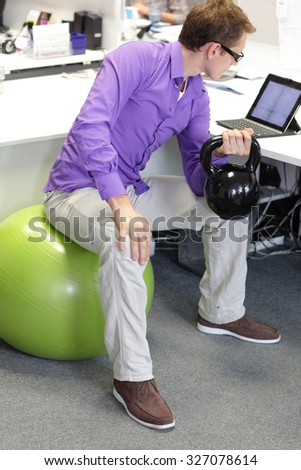 man on ball working out with kettlebell during ofice work - stock photo