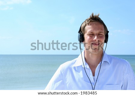 Man on beach listening to headphones with eyes closed