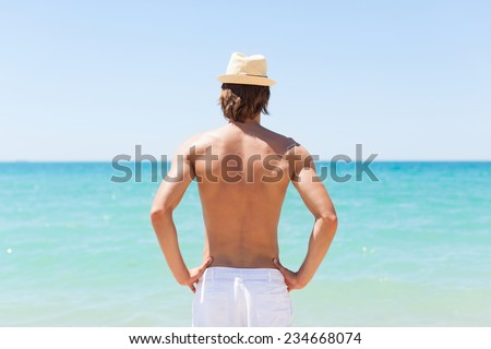man on beach rear view guy wearing summer hat, standing back looking to sea blue sky horizon, vacation concept of freedom travel ocean