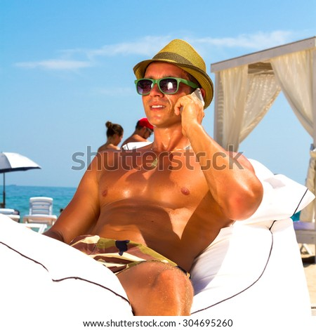 Man on beach sitting on beach chair looking to side smiling and talking on mobile phone,wearing hipster hat and military print trousers.Young male model enjoying summer travel holiday by the ocean. - stock photo
