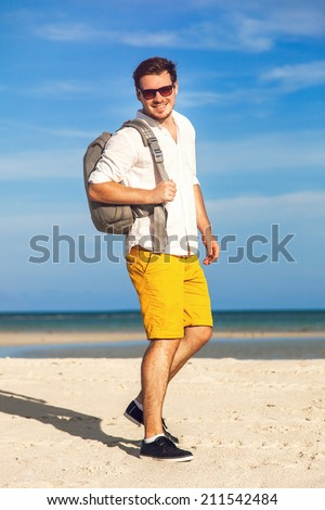Man on beach  smiling and happy wearing hipster bright outfit. Young male model enjoying summer travel holiday by the ocean with stylish backpack - stock photo