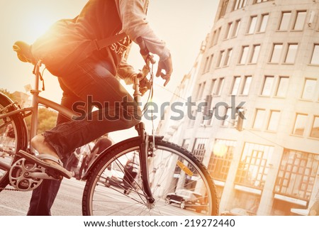 Man on bike in traffic with sunflare  - stock photo