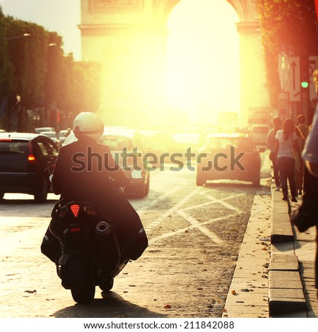 man on bike rides in Paris on road in morning at sunrise - stock photo