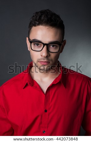 Man on black background in red shirt and glasses. Business style. Fashion