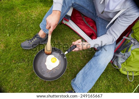 Man On Camping Holiday Frying Egg In Pan