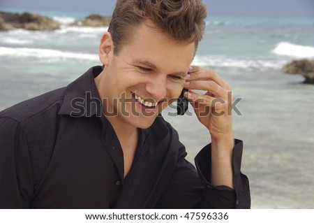Man on cellphone at beach - stock photo
