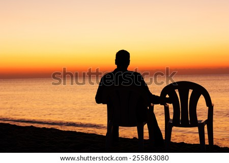 Man on chair alone - stock photo