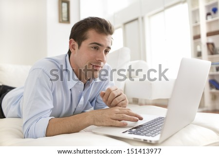 Man on couch using laptop at home