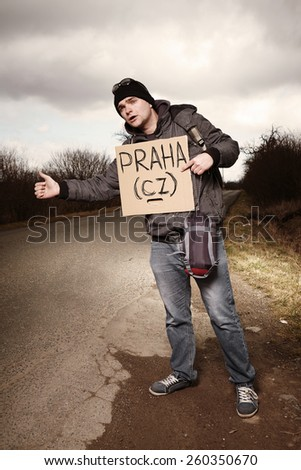 Man on Czech route trying to stop car for hitch-hiking to Prague - stock photo
