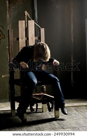 Man on electric chair. Dramatic studio lighting - stock photo