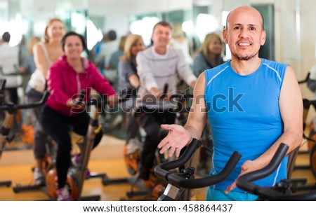 Man on fitness cycle training with  people