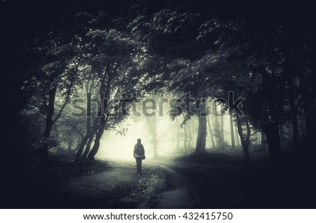 man on forest path in fog - stock photo