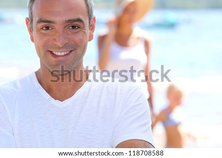 Man on holiday with his family - stock photo