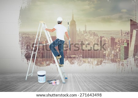 Man on ladder painting with roller against room with large window looking on city - stock photo
