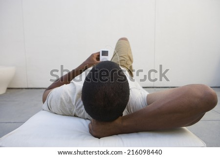 Man on lounge chair with MP3 player, rear view - stock photo