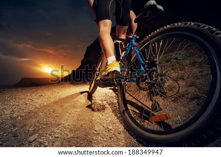 Man on mountain bike rides on the trail on a beautiful sunset. Bicycle wheel closeup.