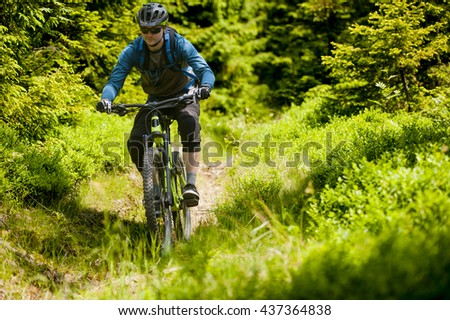 Man on mountain bike rides on trail in the forest. - stock photo