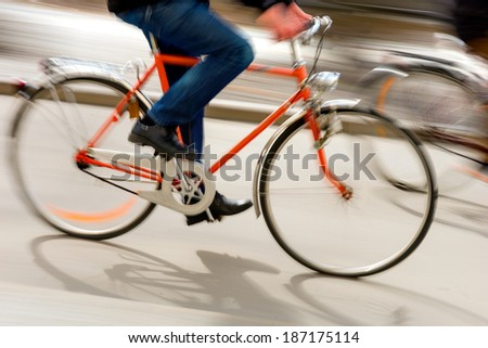 Man on orange bike in city in blurred motion - stock photo