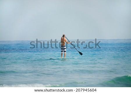 man on paddleboard over sea - stock photo