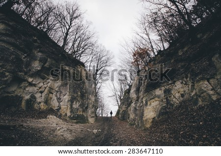 man on path between cliffs - stock photo